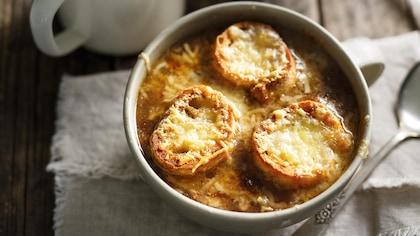 Un bol et des tasses contenant de la soupe à l'oignon avec du pain gratiné.