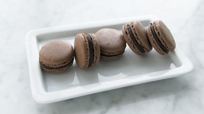 Cinq macarons sont disposés dans une assiette rectangulaire.