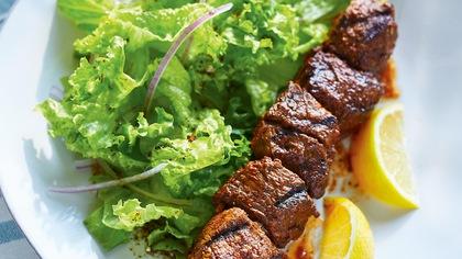 Une brochette de bœuf épicé accompagnée d'une salade verte et de deux quartiers de citron.