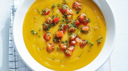 Un bol de crème de pois jaunes cassés aux tomates.