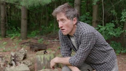 Un homme aux cheveux grisonnants. Il est dans la forêt et semble découragé.