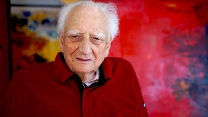 L'homme porte un chandail rouge. Il pose devant une peinture abstraite.