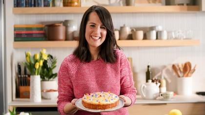 Geneviève O'Gleman tient un gâteau décoré avec des fleurs.