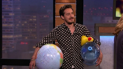 Il tient un canard en plastique, un cruchon et un globe terrestre dans ses mains.