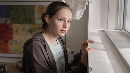 La jeune fille regarde par une fenêtre