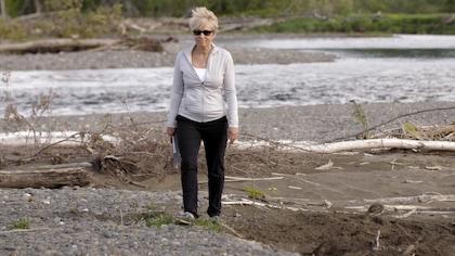 Elle marche sur le bord d'une rivière.