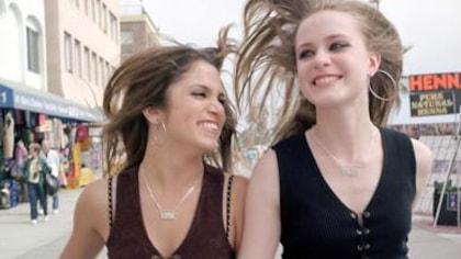 Deux jeunes filles marchent en riant dans la rue.