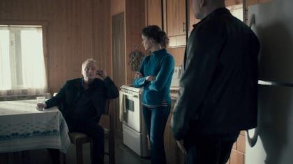 Une femme est dans une cuisine avec deux hommes.