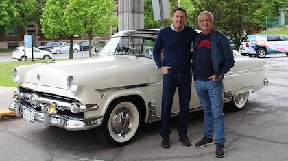 Patrice Roy et Michel Barrette devant une voiture blanche.