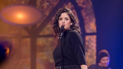 Elle chante sur scène et un micro sur pied est devant elle.