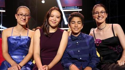 4 adolescents assis côte à côte sur un canapé.
