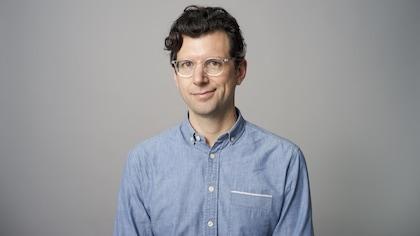Un homme qui porte une chemise bleue.