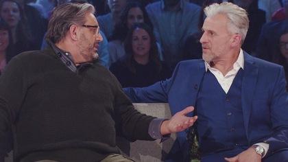 Les deux invités discutent sur le divan.