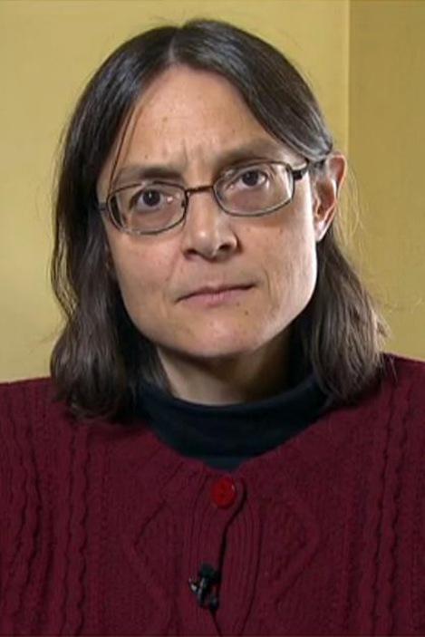 Une femme, assise dans un bureau, regarde vers la caméra.