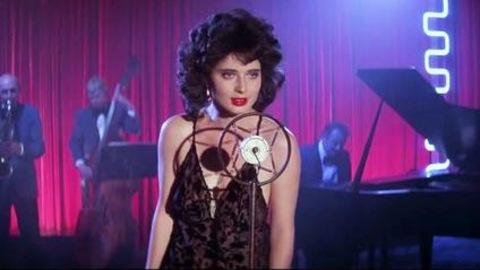 Une femme brune devant un micro, un orchestre derrière elle, sur une scène.