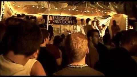 Une foule de jeunes gens devant un stand, la nuit.
