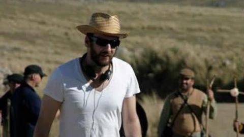 Un homme (Ken Scott) en chapeau de paille et lunettes de soleil, des écouteurs autour du cou.