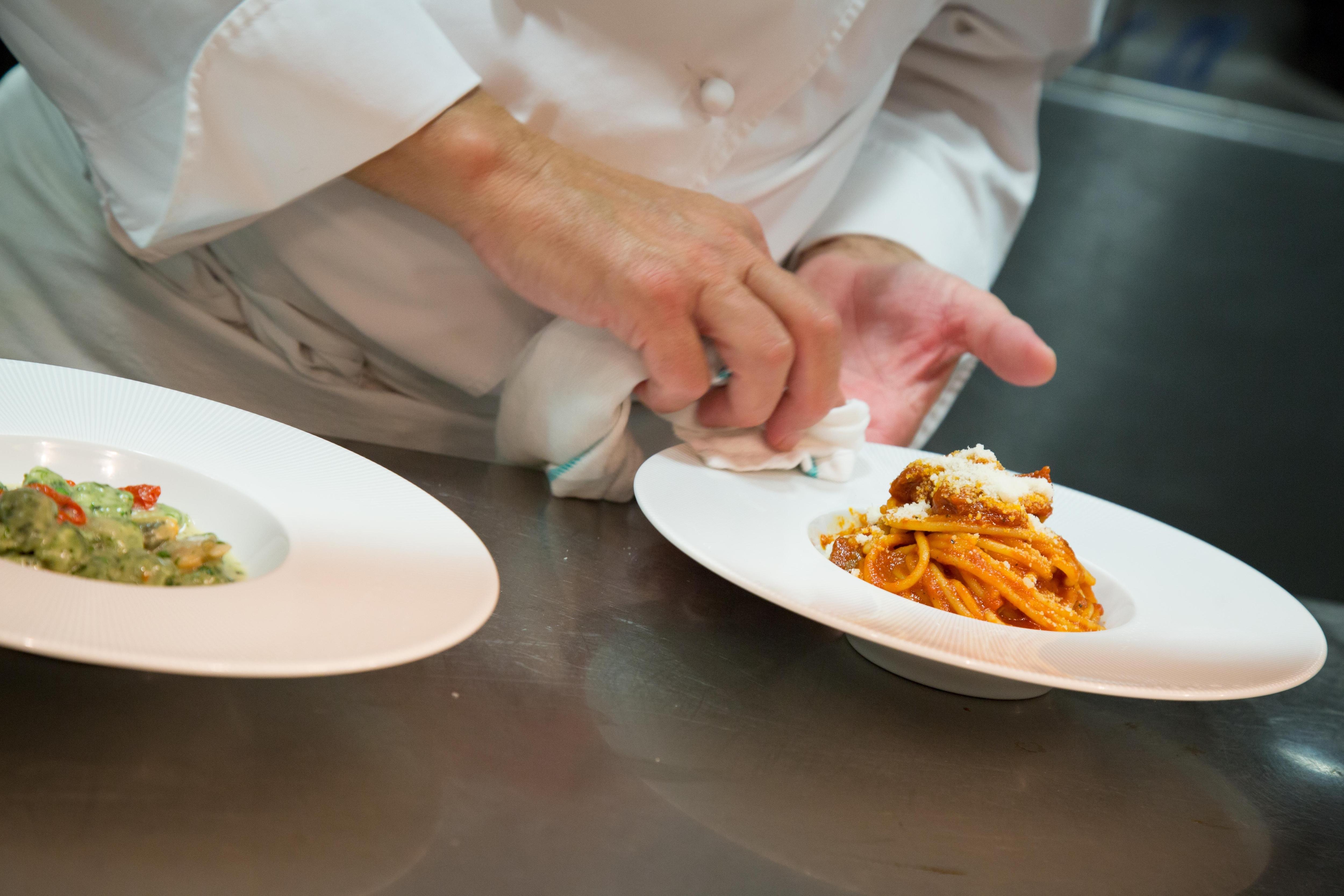 Un chef nettoie le bord d'une assiette de pâtes.