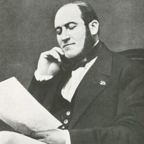 Image de l'homme barbu, assis, en pleine lecture d'un document.