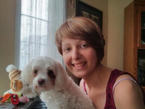 Jenifer, souriante, pose avec son chien