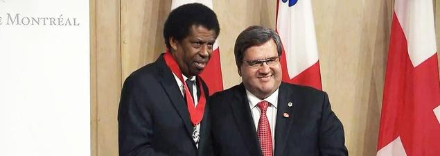 L'écrivain Dany Laferrière serre la main du maire de Montréal Denis Coderre après avoir été fait mercredi officier de l'Ordre de Montréal.