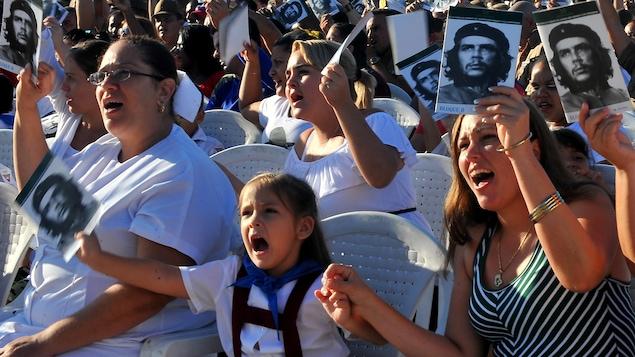 Des Cubaines assises sur des chaises blanches brandissent des photographies d'Ernesto «Che» Guevara lors d'une commémoration du 50e anniversaire de sa mort à Santa Clara
