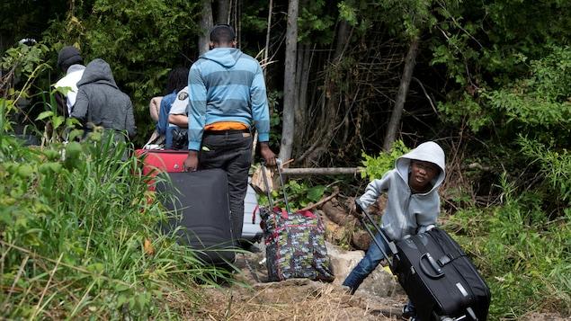 Une famille transporte des bagages alors qu'ils traversent la frontière pour demander asile au Canada.
