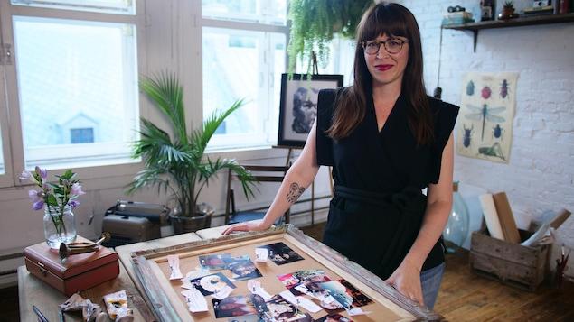 Elle porte une chemise noire. Elle pose devant son tableau d'affichage.