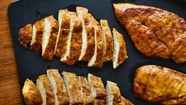 Poitrines de poulet marinées à l'érable sur une planche à découper.
