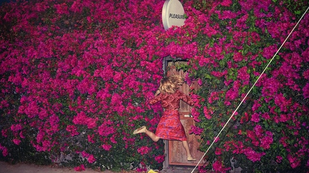 "A woman jumps in front of a wooden door that's set in a large wall of pink rhododendron bushes. A circular sign above the door has one word on it, ""Pleasure."""