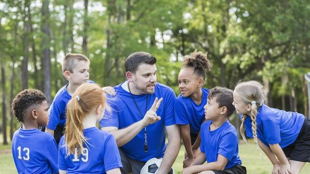 Des enfants avec leur coach de soccer.