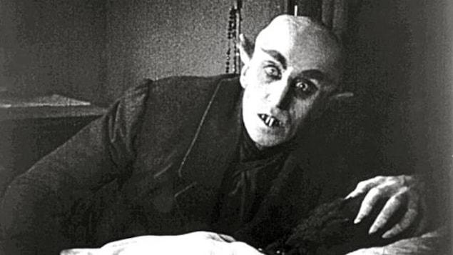 Le personnage de Nosferatu penché sur sa victime.