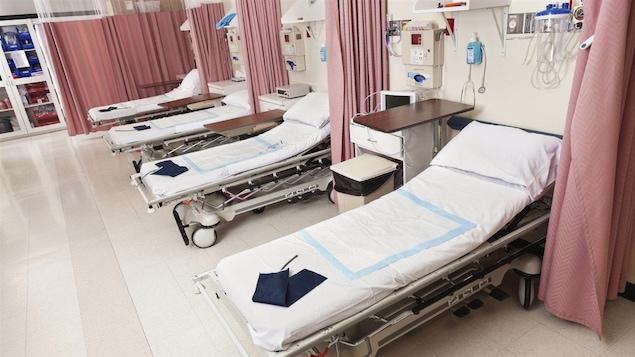 Photo de 4 lits séparés par des rideaux à l'urgence.