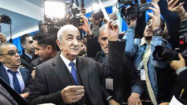 Abdelmadjid Tebboune lève son bulletin de vote avant de le placer dans l'urne.