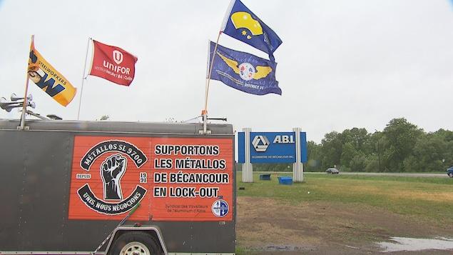 Une insigne où on peut y lire « Supportons les métallos de Bécancour en lock-out » est apposée sur un camion. Plusieurs drapeaux flottent au vent. L'insigne de la compagnie ABI est en arrière-plan.