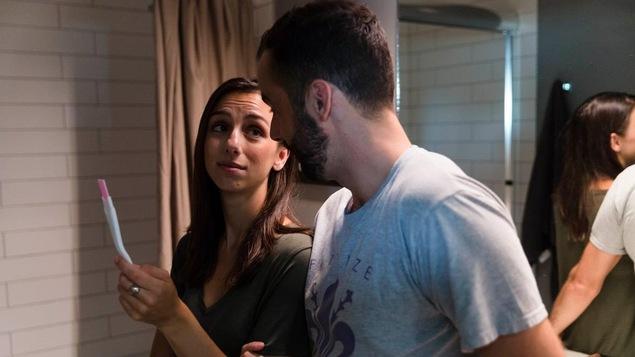 Une femme montre un test de grossesse à un homme.