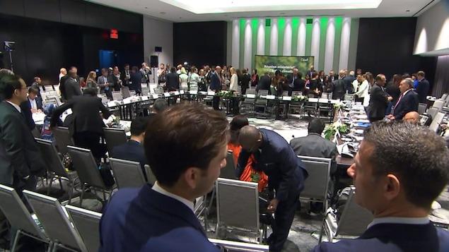 Une trentaine de personnes discutent et s'activent autour d'une grande table carrée où sont placées plusieurs rangées de chaises.