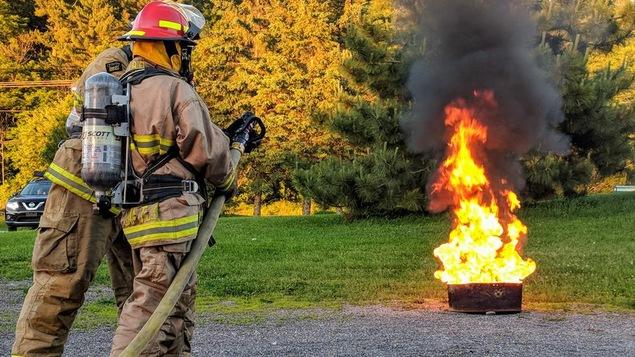 Deux pompiers devant un feu