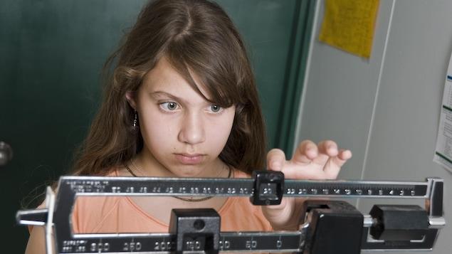 Une jeune fille se pèse sur la balance, elle a l'air inquiète à propos de son poids.