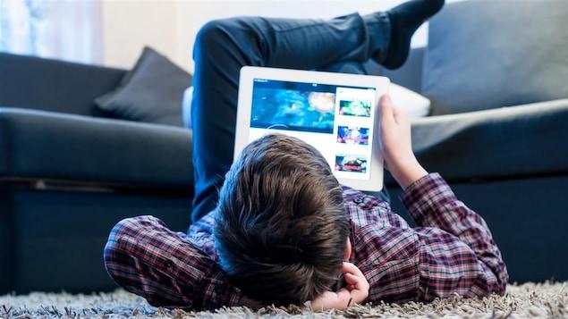 Un adolescent regarde une tablette allongé sur le sol du salon.