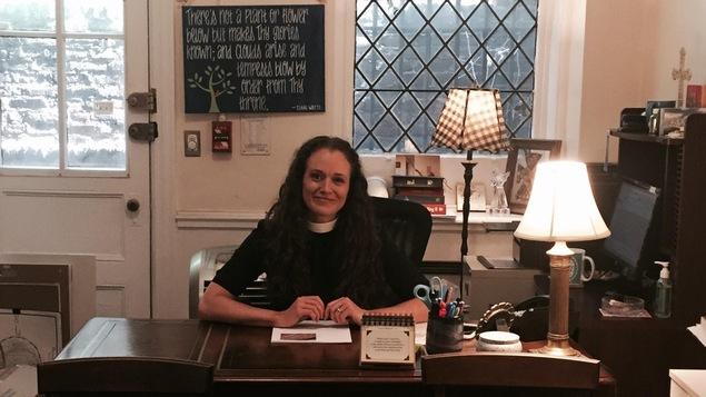 Une jeune femme souriante, assise à son bureau
