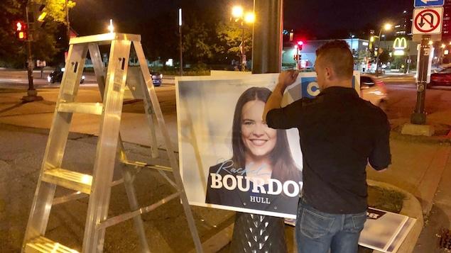 Un homme installe des affiches de la Coalition Avenir Québec sur un poteau dans une rue du secteur Hull à Gatineau.