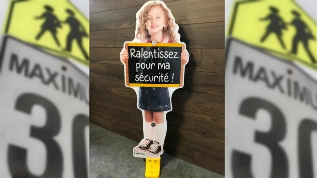 Une affiche d'une fillette tenant un tableau disant «Ralentissez pour ma sécurité».