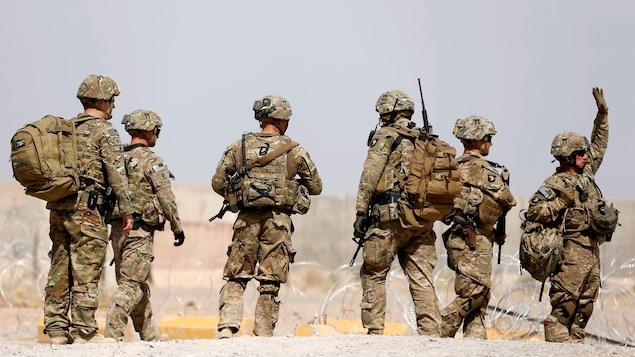 Six soldats américains marchent sur un sol terreux, le long d'une clôture de barbelés.