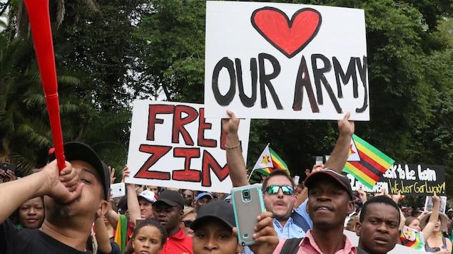 Des manifestants brandissent des pancartes réclamant le départ du président Robert Mugabe à Harare, au Zimbabwe.