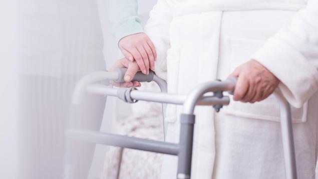 Une femme âgée s'appuie sur une marchette.