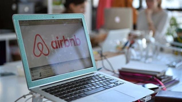 Le logo d'Airbnb s'affiche sur un écran d'ordinateur portable dans une salle de travail.