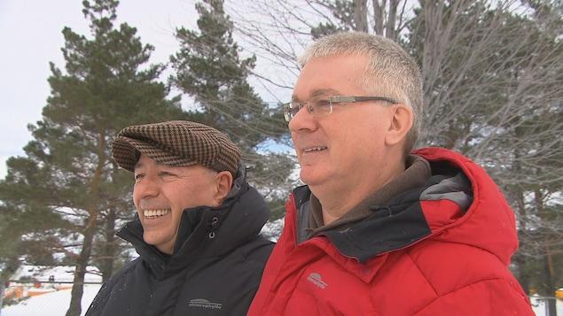 Alain et Nelson sourient en se tenant par les épaules.