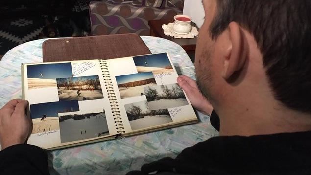Un homme, vu de dos, qui regarde un album de photos