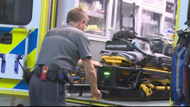 Un ambulancier tire une civière dans une ambulance.